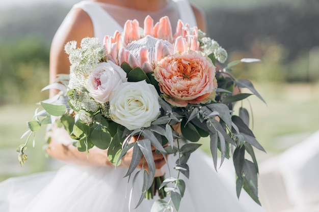 Bride holds the beautiful bridal bouquet with roses, eucalyptus and giant protea