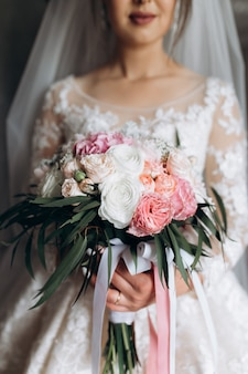 Bride holds the beautiful bridal bouquet with white and pink roses