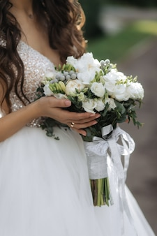Bride holds the beautiful bridal bouquet with white roses and peonies