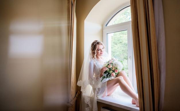 Невеста держит красивый свадебный букет, сидящий на подоконнике