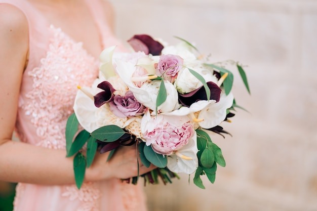 The bride holds a bouquet of roses, calla lilies, peonies and eucalyptus branches.
