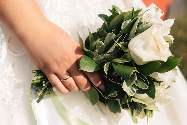 The bride holds a bouquet of white roses on the background of a white wedding dress.