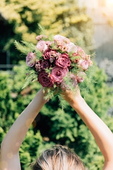 Bride holds a bouquet of wild flowers over her head close up