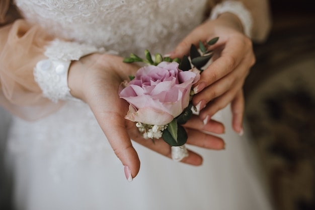 Bride holds a butonholle with pink rose