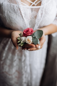 Bride holds a butonholle with pink and white roses