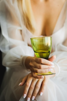 The bride holds a glass of champagne.