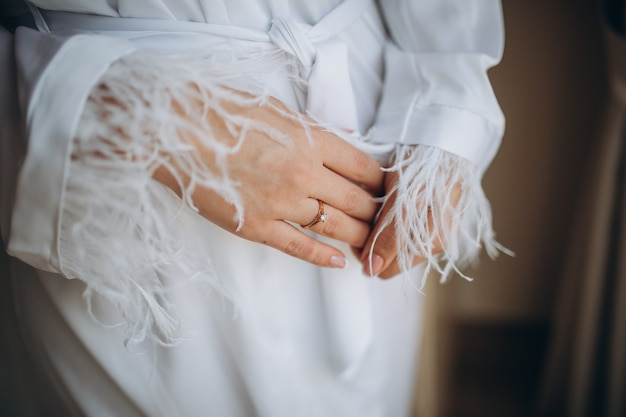 The bride holds a gold wedding ring with a diamond
