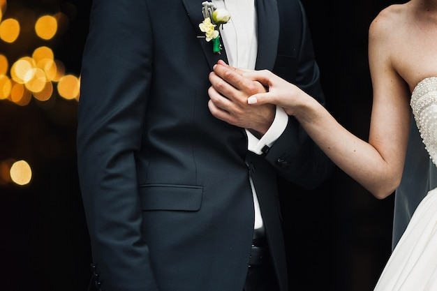 Bride holds groom's hand while they stand outisde
