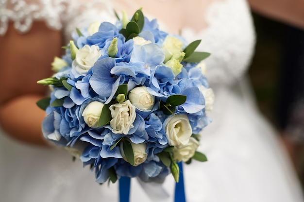 Bride holds in her hand a beautiful wedding bouquet of roses and blue hydrangeas