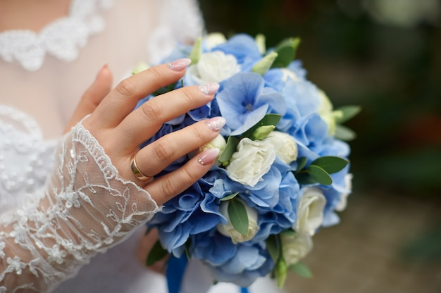 Bride holds in her hand a beautiful wedding bouquet of roses