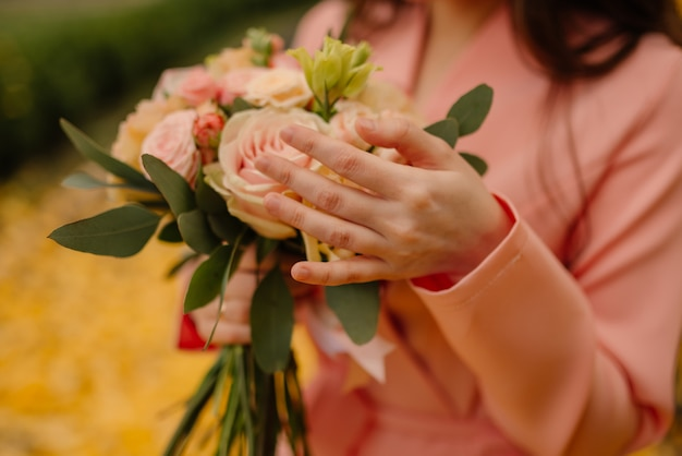 Bride holds in her hands a wedding bouquet