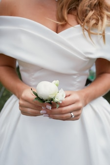 Bride holds in her arms little white boutonniere