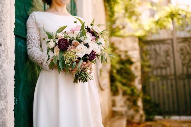 花嫁は彼女の手で緑のドアにもたれて美しい花の花束を持っています