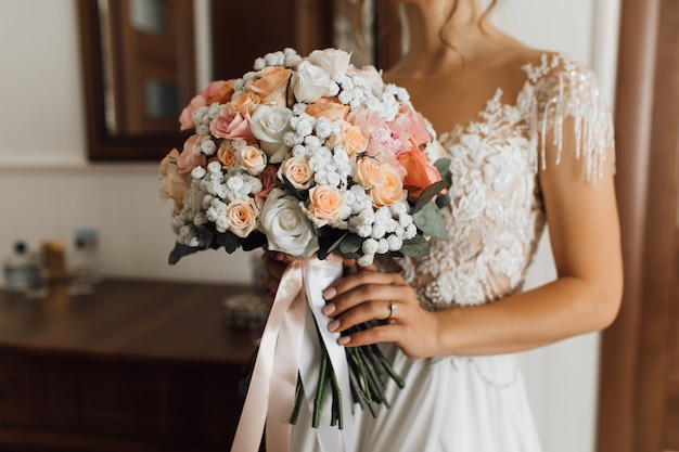 Bride holds the lush bouquet with delicate flowers colors