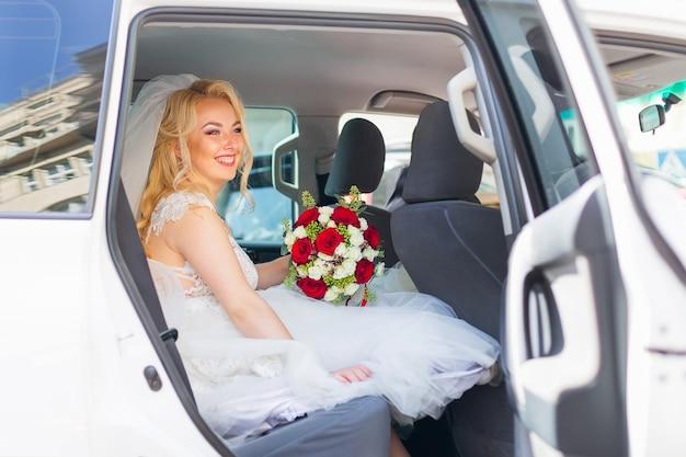 花嫁はウェディングブーケを持って、シックな車の後部座席に座っているカメラをのぞき込む