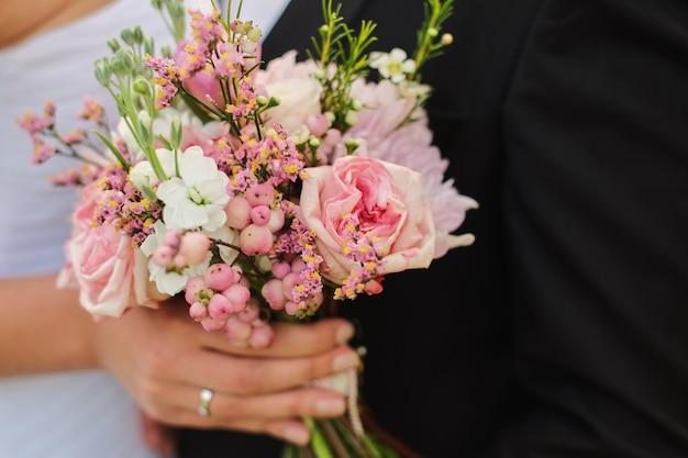 Bride holds a wedding bouquet in hands, the groom hugs her