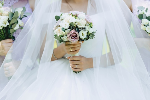The bride holds a wedding bouquet in her hands
