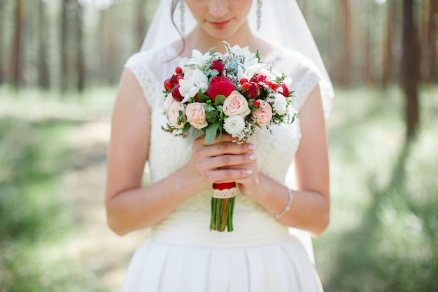 花嫁は花と白いドレスで白と赤の花の屋外の若い女の子のウェディングブーケを保持します