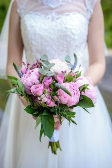 The bride holds a wedding bouquet of peonies closeup
