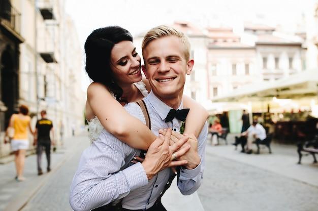 Bride hugging her boyfriend from behind