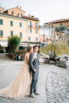 コモ湖の堤防に立ち、新郎の後ろから抱き合う花嫁