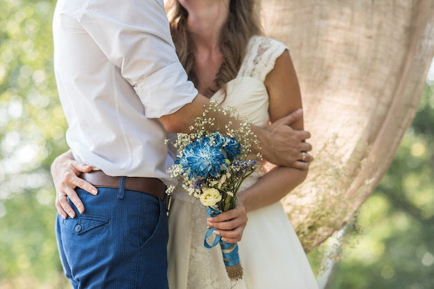 The bride hugs the groom and holds a bridal bouquet with blue flowers on a background of the forest