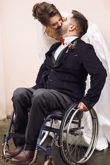 Bride hugs groom on the wheelchair from behind posing on the street