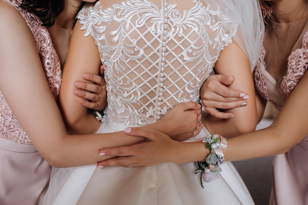 Bride hugs with her bridesmaids
