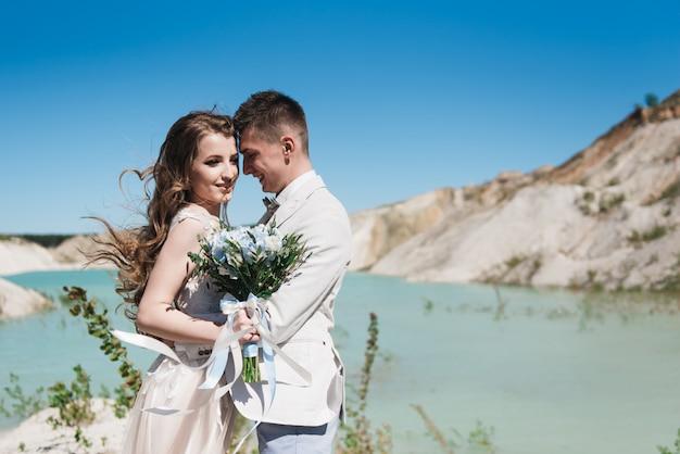 호수 근처에 가벼운 소송에서 신랑을 포옹하는 아름 다운 드레스의 신부. 야외에서 모래 언덕에 웨딩 커플 서. 낭만적 인 사랑 이야기. 수평선에 푸른 푸른 물.