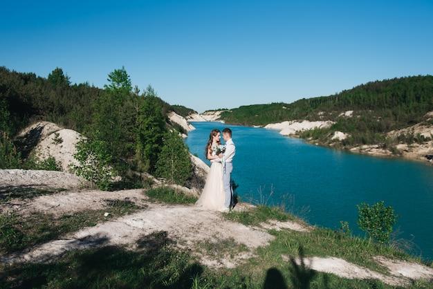 호수 근처에 가벼운 소송에서 신랑을 포옹하는 아름 다운 드레스의 신부. 야외에서 모래 언덕에 웨딩 커플 서.