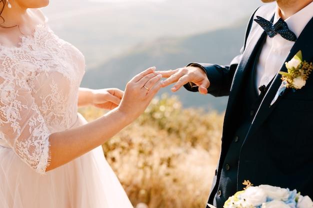 Невеста в красивом платье надевает кольцо на палец жениха