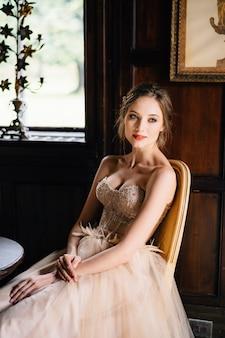 美しいドレスを着た花嫁は、古い建物のテーブルの椅子に座っています
