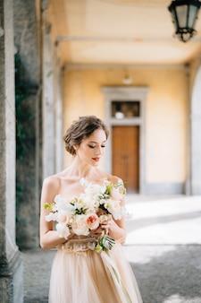ピンクの花の花束と美しいドレスを着た花嫁は、アーチ型の廊下のコモ湖に立っています