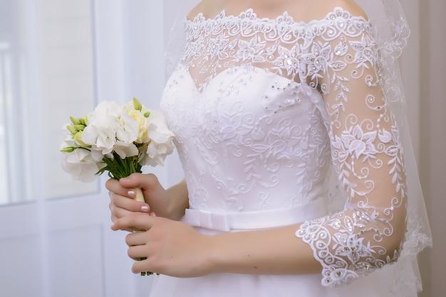 Невеста в красивом кружевном платье держит свадебный букет из белых цветов крупным планом