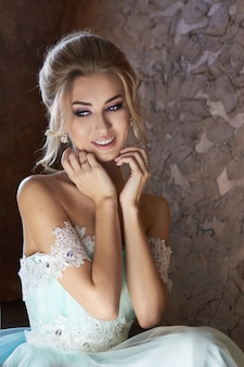 結婚式を見越して美しいターコイズブルーのドレスを着た花嫁。レースのドレスシーグリーンのブロンド。幸せな花嫁、感情、彼の顔の喜び。美しいメイクマニキュアと髪型の女性