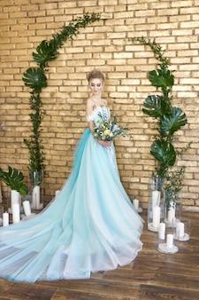 결혼식을 기대하고 아름다운 청록색 드레스의 신부. 부케와 레이스 드레스 바다 녹색 금발. 행복한 신부, 감정, 그의 얼굴에 기쁨. 아름다운 메이크업, 매니큐어 및 헤어 스타일 여성