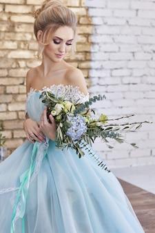 結婚式を見越して美しいターコイズブルーのドレスを着た花嫁。花束とレースのドレスシーグリーンのブロンド。幸せな花嫁、感情、彼の顔の喜び。美しいメイク、マニキュア、ヘアスタイルの女性