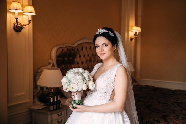 아름다운 웨딩 드레스를 입은 신부는 웨딩 부케를 들고 카메라를 바라 봅니다. 아늑한 침실의 배경에 신부입니다.