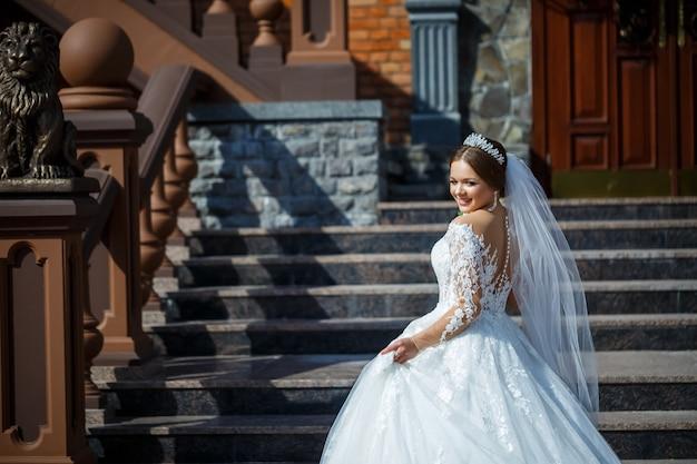 れんが造りの建物の背景に美しい白とロングドレスの花嫁