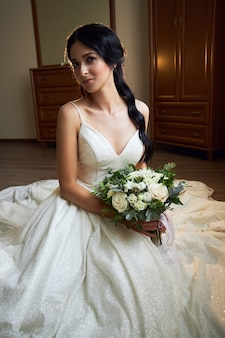 Невеста в красивом белом платье с букетом цветов в руках ждет свадебной церемонии.