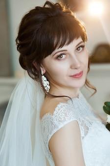 아름 다운 하얀 드레스를 입고 신부는 결혼식을 위해 준비 중입니다. 신부의 아침