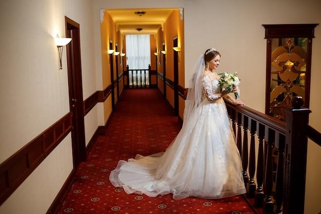 彼女の手に花束を持って結婚式の日に美しい白いドレスを着た花嫁