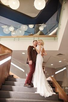 電車の中でシックなロングドレスを着た花嫁と花婿が大きな階段に立ち、愛するカップルが階段で抱き合ってキスをし、お互いを見つめます。結婚式当日、婚姻届当日の夫婦