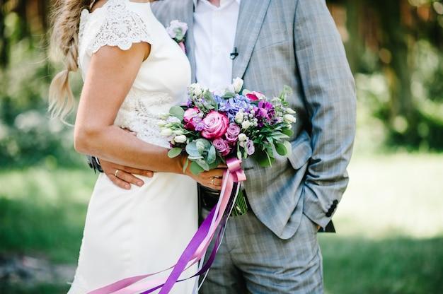 Невеста в платье и жених стоят в зеленом саду и держат в руках свадебный букет цветов и зелени. свадебная пара обнимаются на природе.