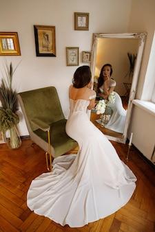 결혼식 날 아침에 거울에 드레스 신부