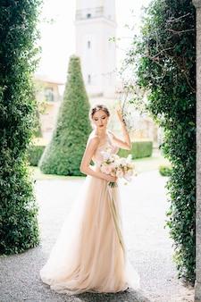 花の花束とドレスを着た花嫁は、緑のツタに対して彼女の頭を下げました
