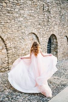 바람에 펄럭이는 핑크색 드레스를 입은 신부가 베르가 모 이탈리아 다시보기의 오래된 거리를 따라 실행됩니다.