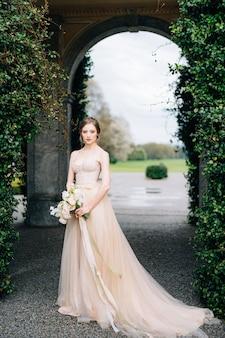 長いドレスの花嫁は花の花束を保持します