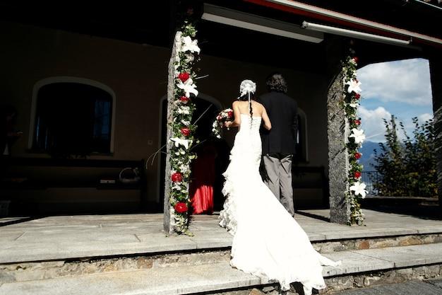 긴 드레스를 입은 신부는 오래된 예배당으로 들어갑니다.