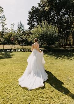 緑の芝生で逃げる長い白いドレスを着た花嫁